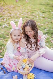 Belle jeune mère et petite fille près d'un magnolia en fleurs. pâques. printemps. fleurs roses.