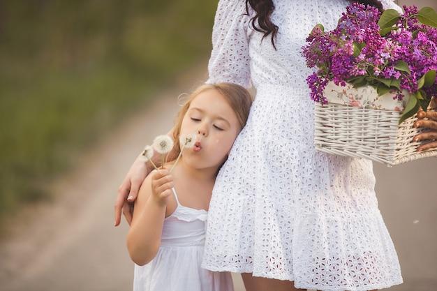 Belle jeune mère et petite fille s'amuser ensemble. jolie maman et jolie fille à l'extérieur. famille joyeuse ensemble. enfant, souffler, blowball