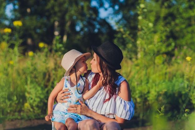 Belle jeune mère et sa fille s'amusant dans le champ de blé.