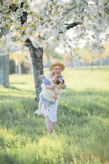 Une belle jeune mère avec sa petite fille se repose sur un pique-nique dans le jardin fleuri