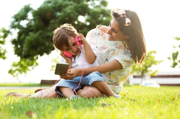 Belle jeune mère avec son fils écoutant de la musique dans le parc.