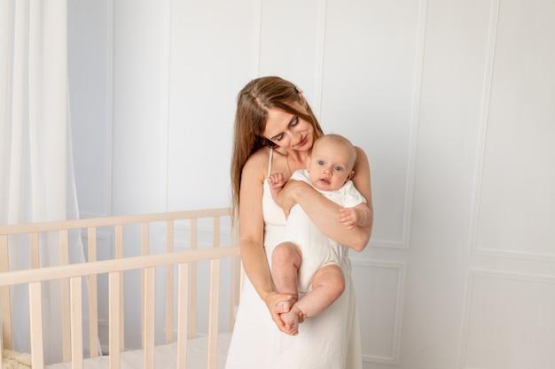 Belle jeune mère tenant sa fille 6 mois dans la pépinière debout près de la crèche