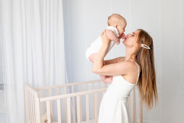 Belle jeune mère tenant sa fille, la serrant dans ses bras et l'embrassant dans la pépinière debout près de la crèche, la fête des mères, place pour le texte