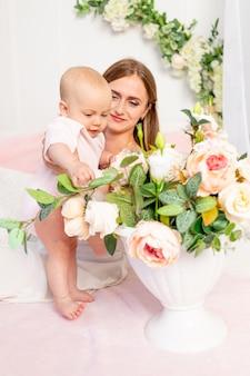 Une belle jeune mère tient sa fille une fille de 6 mois sur un lit blanc et regarde des fleurs