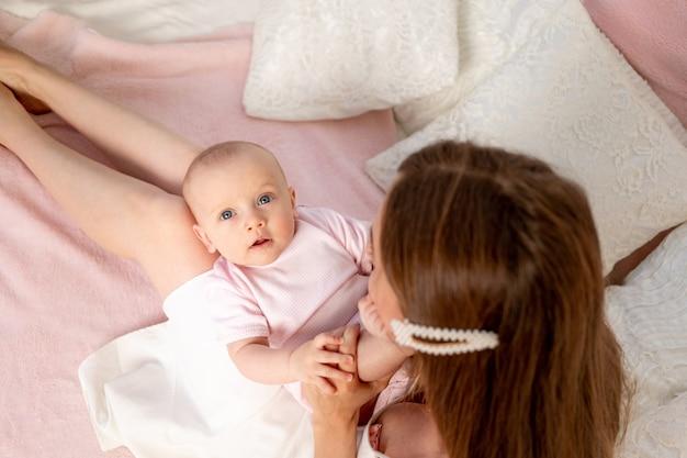 Une belle jeune mère tient sa fille une fille de 6 mois sur ses genoux sur un lit blanc, jouant et l'embrassant