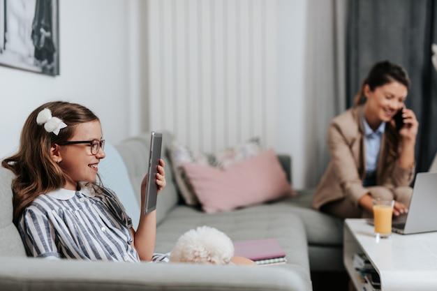 Belle jeune mère travaillant à domicile pendant que sa fille regarde des cours en ligne. distanciation sociale et mode de vie covid-19 ou coronavirus.