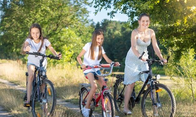 Belle jeune mère à vélo avec deux filles au pré