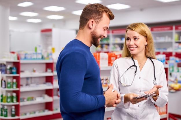 Belle jeune pharmacien caucasien travaille avec le client dans une pharmacie moderne