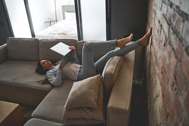 Belle jeune pigiste caucasienne moderne concentrée et décontractée avec un ordinateur portable allongé sur le canapé