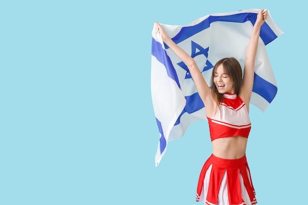 Belle jeune pom-pom girl avec le drapeau d'israël sur bleu