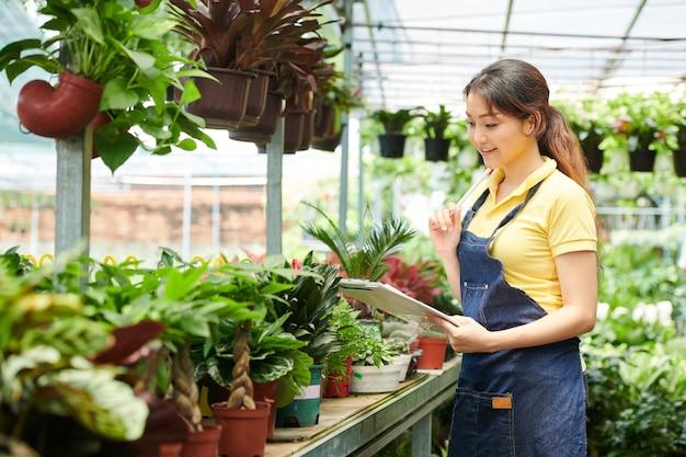 Belle jeune propriétaire de magasin de fleurs vérifiant les plantes et tenant des registres de ce qui est vendu plus souvent