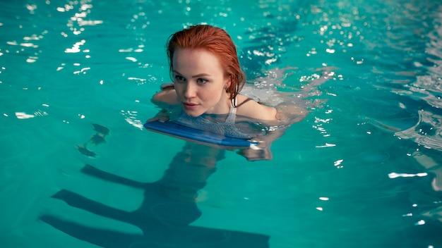Belle jeune rousse caucasienne nage dans la piscine couverte.
