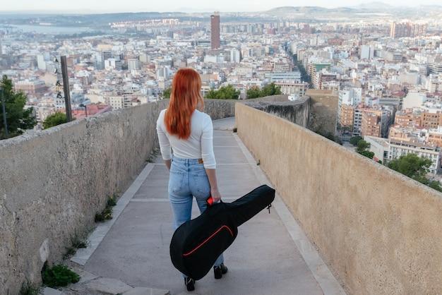 Belle jeune rousse se promène avec sa guitare à l'extérieur le long d'un mur qui offre une vue panoramique sur la ville