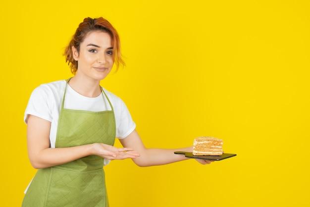 Belle jeune rousse tenant une tranche de gâteau et regardant la caméra