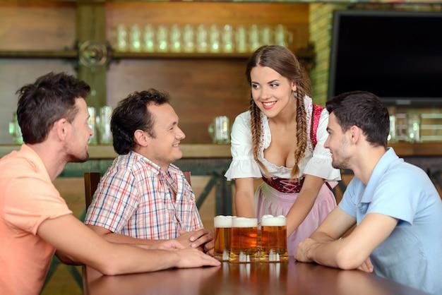 Belle jeune serveuse servant de la bière alors que trois hommes.