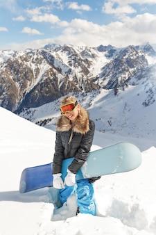 Belle jeune snowboardeuse avec snowboard bleu sur le versant de la montagne