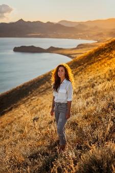 Une belle jeune touriste est assise au sommet d'une montagne et profite de la vue sur le coucher de soleil