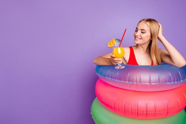 Belle jolie dame avec des flotteurs colorés autour de la taille tenant un cocktail