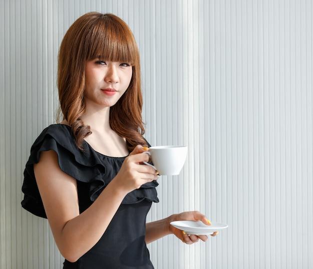 Belle jolie femme asiatique adolescente tenant une tasse de café blanche avec un visage heureux, concept pour l'heure de la pause.