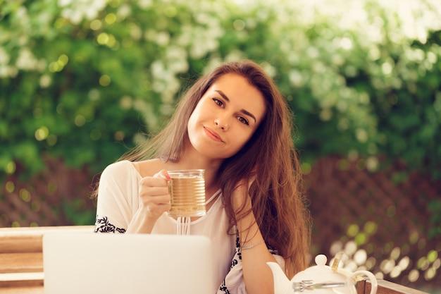 Belle jolie femme au café avec un ordinateur portable ayant une pause-café