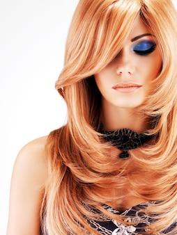 Belle jolie femme aux longs poils rouges. portrait de jeune mannequin avec le maquillage des yeux bleus isolé sur un mur blanc