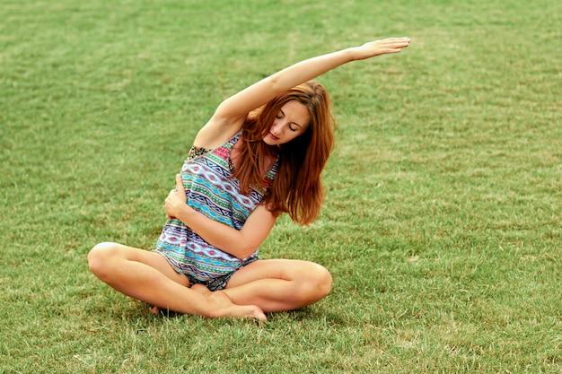 Belle jolie femme faisant des exercices de yoga dans le parc. concept sain et yoga. fitness et sport