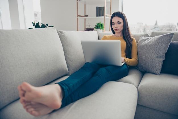 Belle jolie femme posant sur le canapé en écrivant