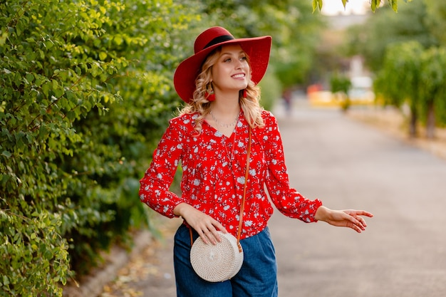 Belle jolie femme souriante blonde élégante en chapeau rouge de paille et tenue de mode d'été chemisier