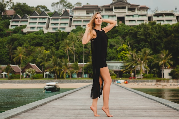 Belle jolie femme vêtue d'une robe noire romantique posant sur la jetée dans un hôtel de luxe,