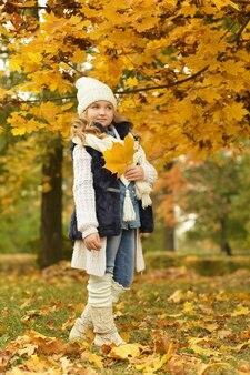 Belle jolie fille en bottes blanches lors d'une promenade quotidienne dans le parc