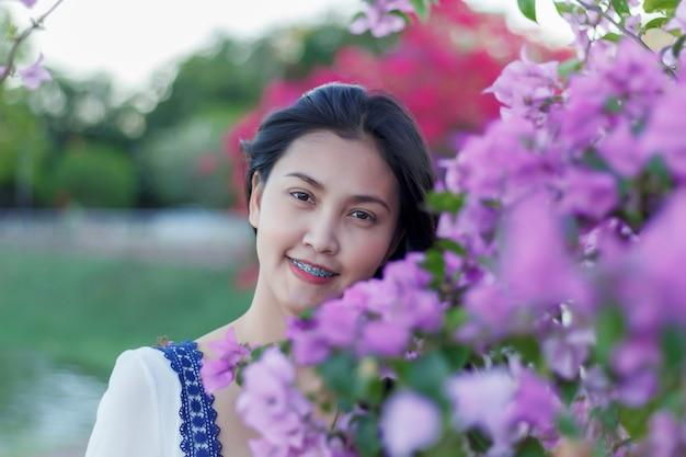 Belle jolie fille avec une fleur colorée dans le parc