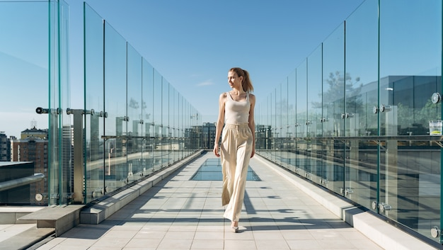 Belle et jolie fille marche sur le toit de la maison. la blonde se repose sur la terrasse
