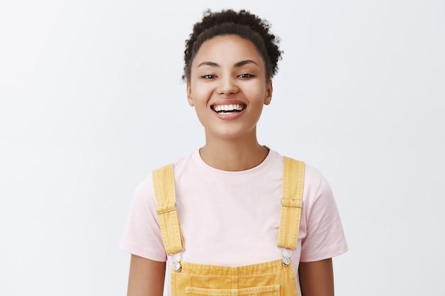 Belle jolie fille en salopette jaune à la mode sur t-shirt souriant largement avec une expression joyeuse et heureuse