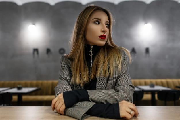 Belle jolie jeune femme avec un beau maquillage dans une veste à carreaux élégante grise dans un t-shirt noir avec un nez percé se trouve à une table dans un café moderne