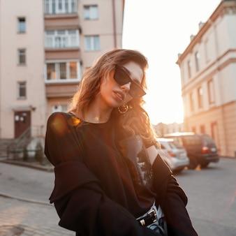Belle jolie jeune femme hipster dans des vêtements à la mode dans un style rétro dans des lunettes de soleil sombres à la mode dans la ville par une journée ensoleillée.