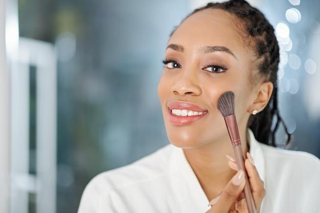 Belle jolie jeune femme noire appliquant le fard à joues pêche sur ses joues lors de la préparation le matin