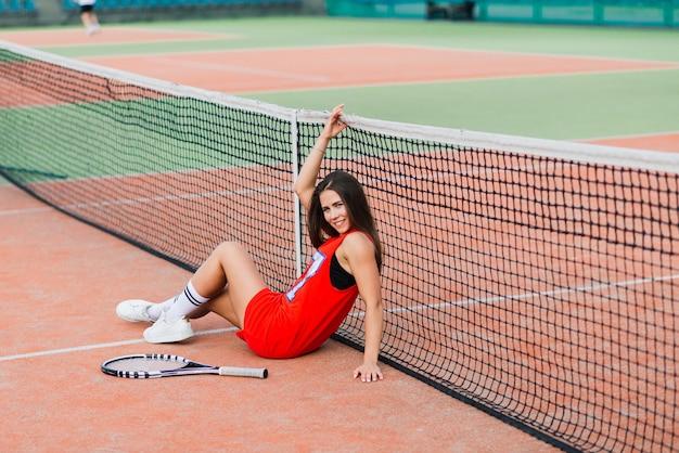 Belle joueuse de tennis sur un court de tennis en robe rouge.
