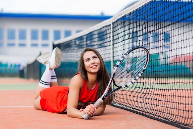 Belle joueuse de tennis sur un court de tennis en robe rouge
