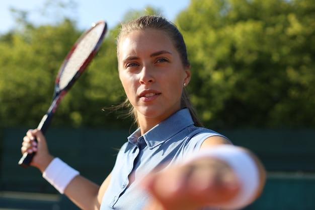 Belle joueuse de tennis servant la balle sur le court de tennis.