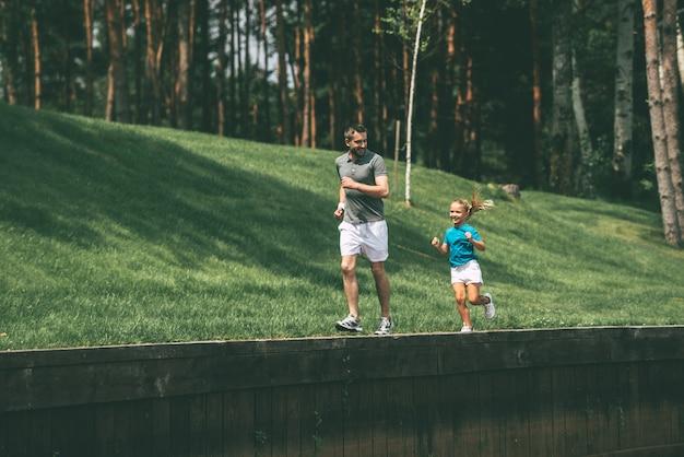 Belle journée pour faire du jogging. toute la longueur du joyeux père et fille faisant du jogging ensemble dans le parc
