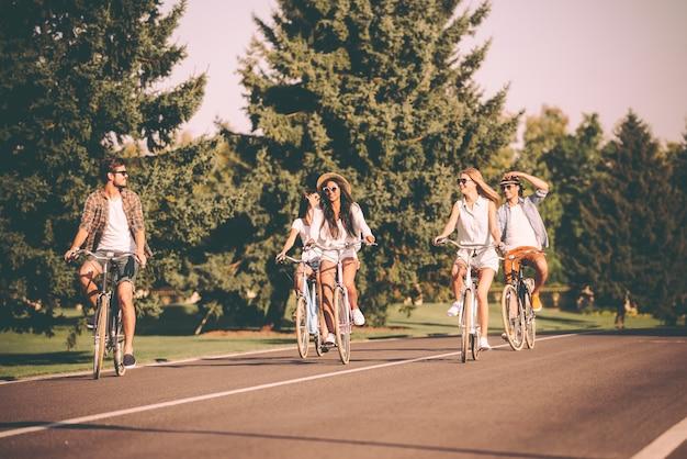 Belle journée pour faire du vélo. groupe de jeunes faisant du vélo le long d'une route et ayant l'air heureux