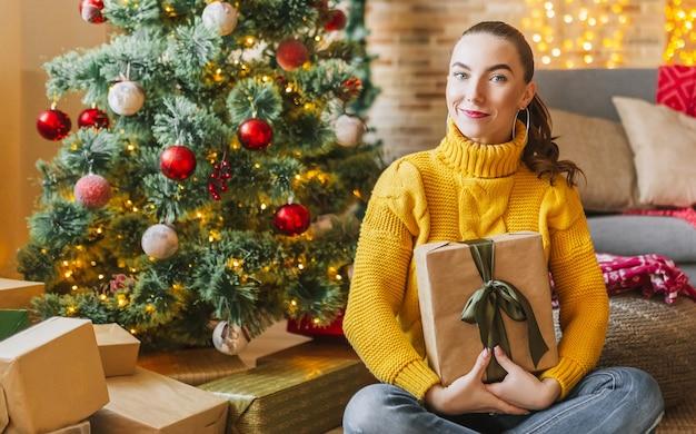 Belle joyeuse jeune fille heureuse avec des cadeaux de noël sur le fond d'un arbre de nouvel an à la maison