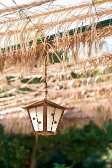Belle lanterne rustique sur une chaîne accrochée à un auvent