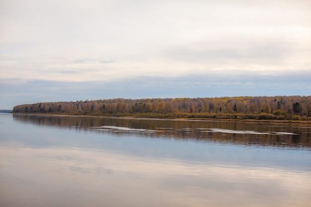 Belle et large rivière automne parmi les bois. endroit calme et tranquille aux couleurs automnales. au milieu de l'île fluviale. vue d'en haut au loin