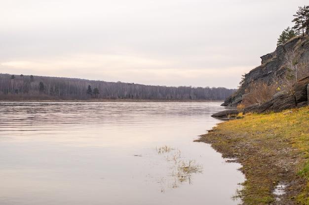 Belle et large rivière d'automne parmi les forêts et le rivage rocheux. un endroit calme et tranquille aux couleurs d'automne. réflexion des nuages dans l'eau par beau temps