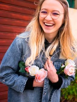 Belle large sourire tartare jeune fille à lunettes avec un bouquet de fleurs.