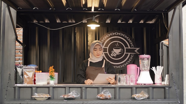 Belle liste de menus de lecture de serveuse asiatique au conteneur de stand de café