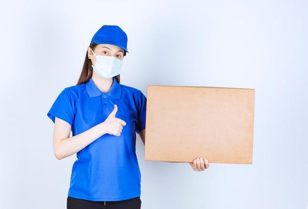 Belle livreuse en masque médical tenant un emballage en carton et levant les pouces.
