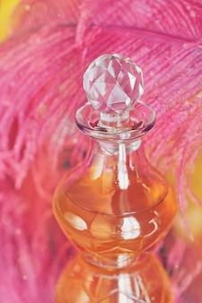Belle lumière abstraite et fond doux flou avec plume violette et bouteille d'huile parfumée ou aromatique