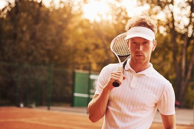 Belle lumière du soleil. un jeune joueur de tennis en tenue sportive est sur le terrain à l'extérieur.